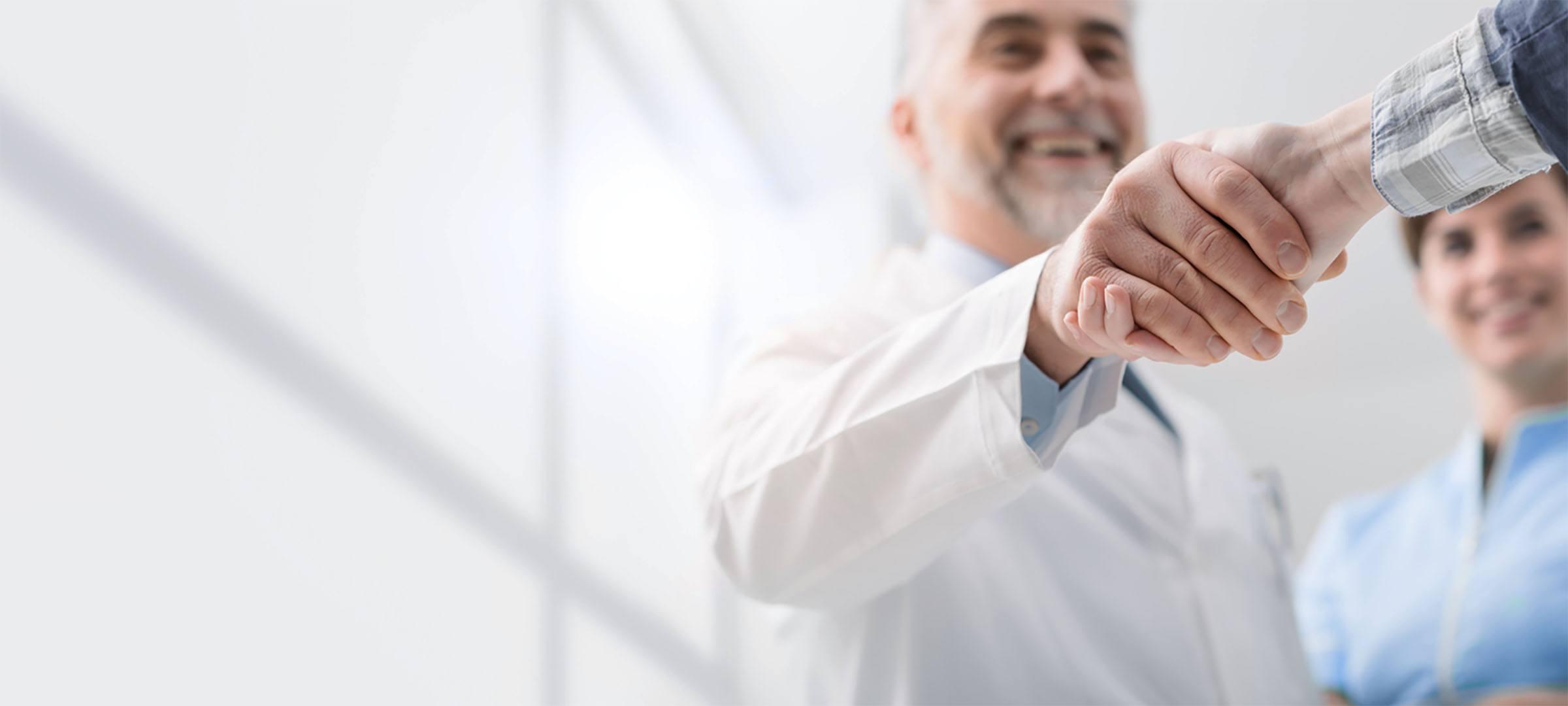 Ärzte schütteln sich nach erfolgreicher Praxisübernahme die Hände.